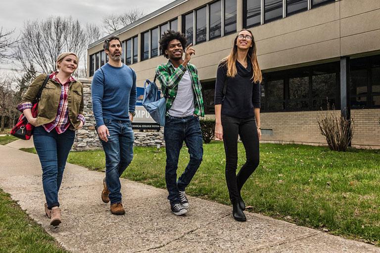 4 Students walking down campus sidewalk.