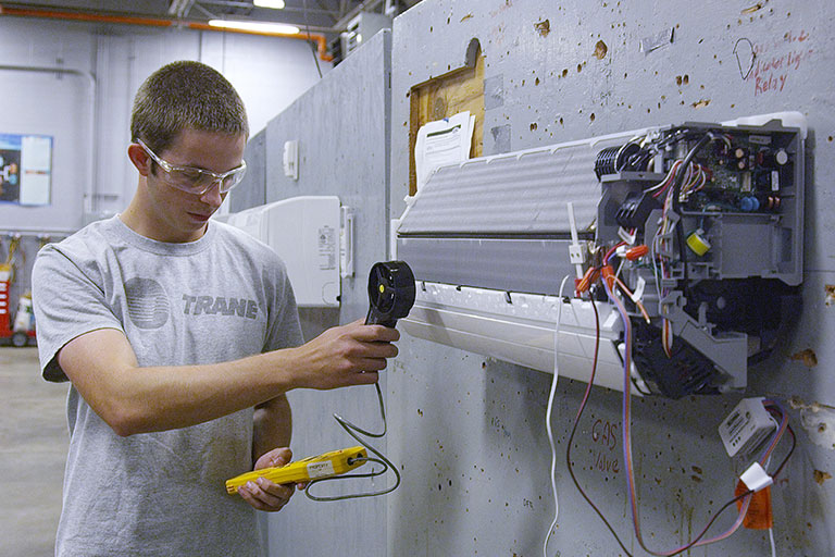 Student inspecting disassembled air conditioner
