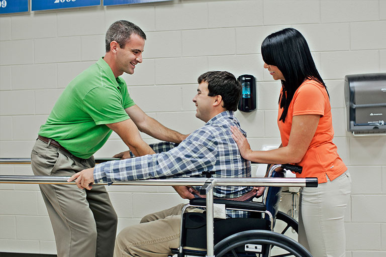 three students practicing physical therapy assistant techniques
